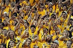 Football stands filled with ASU students, yelling and giving giving the Fork-em-Devils hand sign